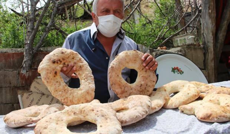 Muhtar kolları sıvadı, köylüler için ekmek pişiriyor
